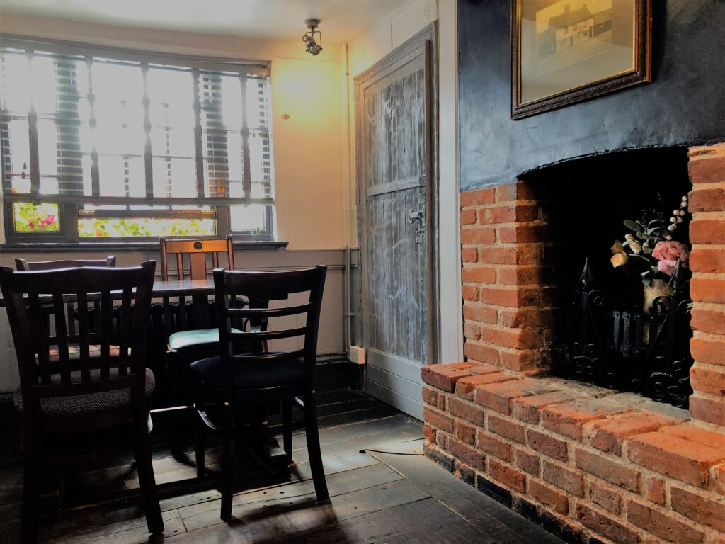 Summer fireplace, dining tables and attractive barge boarded interior at The Barge Inn Battlesbridge Essex