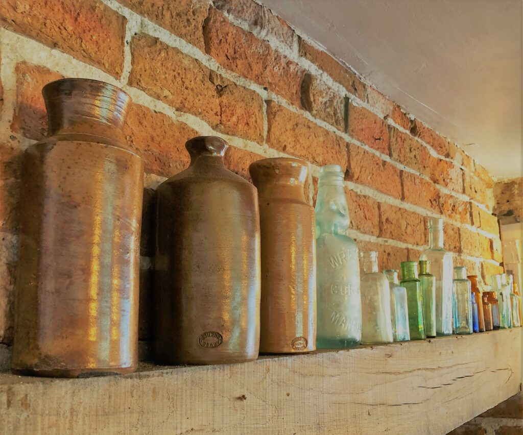 old glass bottles historic glass bottles and attractive barge boarded interior at The Barge Inn Battlesbridge Essex